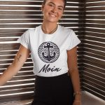 """Junge Frau mit einem weissen T-Shirt von TeeFarm auf dem """"Moin"""" steht"""